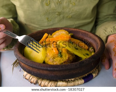 Tasty dinner, Moroccan Tagine and human hand. - stock photo