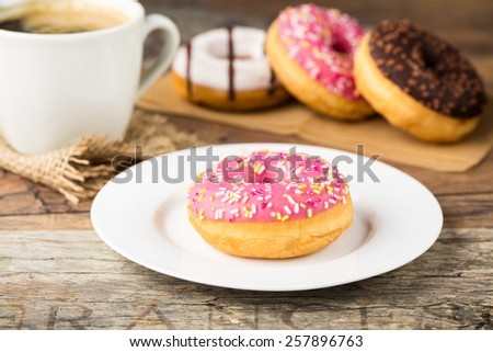 tasty donut with sprinkles and  fresh brewed coffee - stock photo