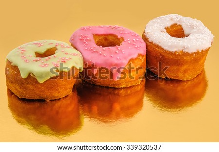 Tasty donuts with reflection on gold background - stock photo