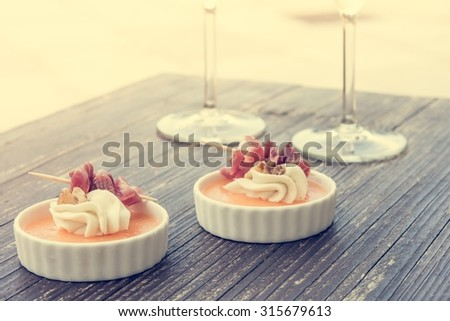Tasty finger food on a wooden table. With a pair of wine glasses. - stock photo