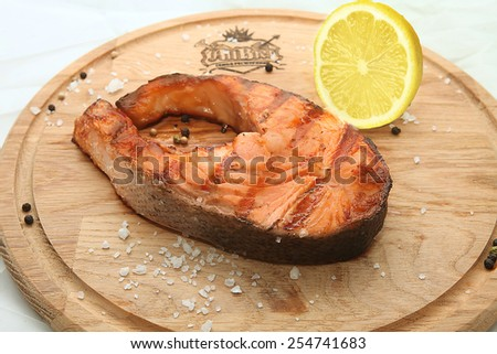 Tasty fish on wooden plate - stock photo
