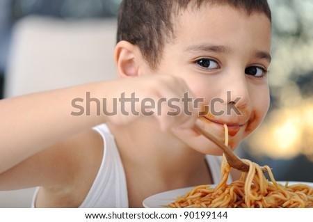 Tasty food, messy child eating spaghetti - stock photo