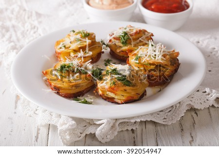 Tasty food: Sliced baked potatoes with Parmesan cheese and dill close-up on the table. horizontal