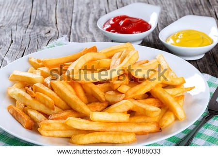 Tasty french fries on a white plate with mustard and tomato sauce in a gravy boat on wooden table background,  close-up, view from above - stock photo