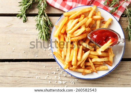 Tasty french fries on plate, on wooden table background - stock photo