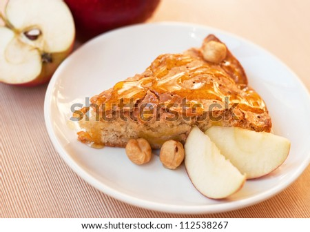 Tasty fresh apple pie with slices of apple and hazelnuts covered with honey on a white plate on a kitchen table - stock photo