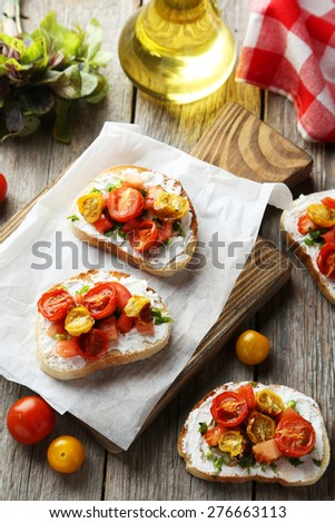 Tasty fresh bruschetta with tomatoes on cutting board on grey wooden background - stock photo