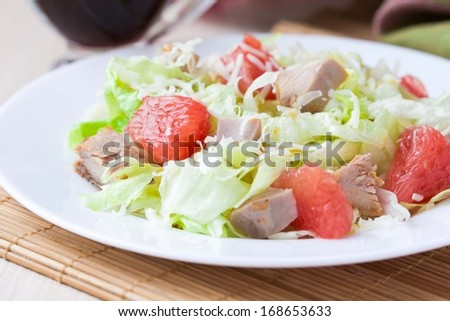 Tasty fresh salad with grapefruit, chicken, lettuce, cheese and sauce, healthy dish - stock photo