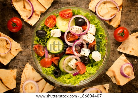 Tasty fresh spring salad and tortilla bread from above on wooden table  - stock photo