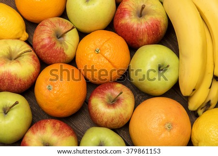 Tasty fruit background with orange, apples and banana on the wooden boards table - stock photo