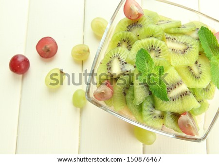 Tasty fruit salad in glass bowl, on white wooden table - stock photo