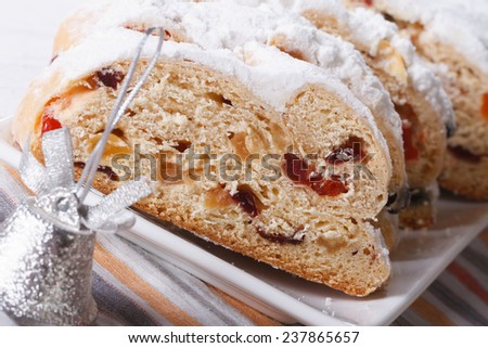 Tasty German Christmas fruit cake Stollen sliced macro on a white plate. horizontal  - stock photo