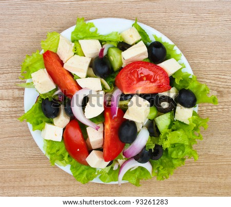 Tasty greek salad on plate on wooden background - stock photo