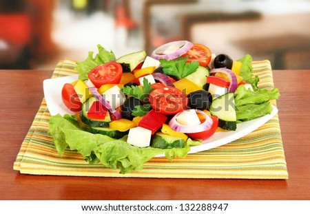 Tasty Greek salad on table in cafe - stock photo