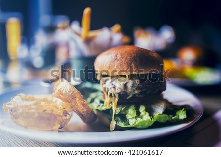 Tasty grilled beef burger with bacon and lettuce, mayonnaise served with french fries - stock photo