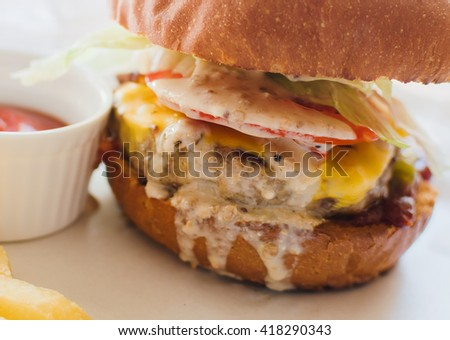 Tasty grilled beef burger with sauce, lettuce and mayonnaise. Closeup of home made burger. Fresh  hamburger closeup. Delicious burgers with beef, tomato, cheese and lettuce. Selective focus. - stock photo
