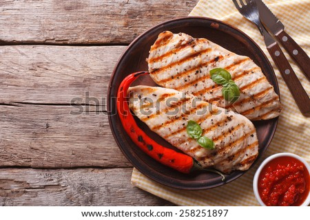 Tasty Grilled chicken fillet and chili peppers on a plate on the table. horizontal view from above