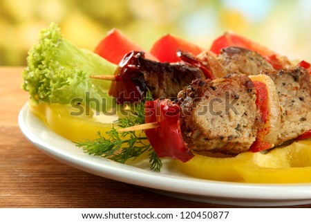 tasty grilled meat and vegetables on skewer on plate, on wooden table - stock photo