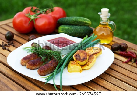 tasty grilled meat sausages  on dish and vegetable - stock photo