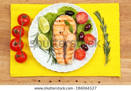 Tasty grilled salmon with vegetables, on wooden table - stock photo
