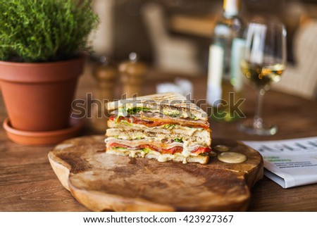 tasty grilled sandwich with sauce on the wooden plate in the restaurant - stock photo