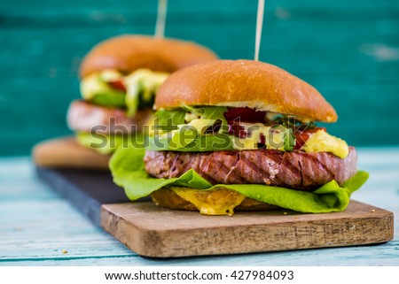 Tasty grilled tuna burger with lettuce and mayonnaise served on wooden table with copyspace - stock photo