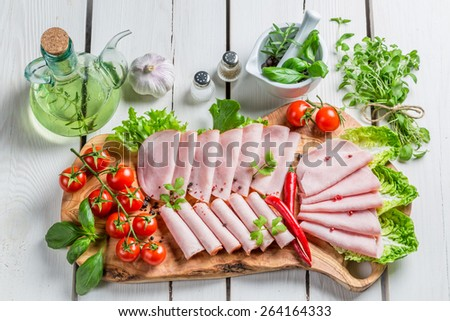 Tasty ham with pepper and herbs - stock photo