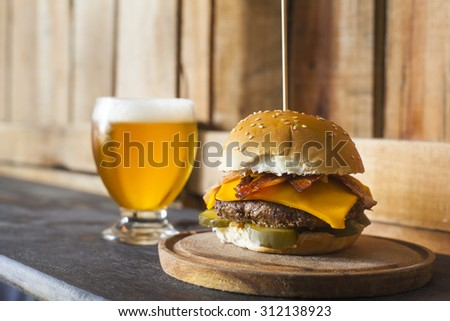 Tasty hamburger with a glass of beer on wooden counter. Pickles, bacon, and cheddar cheese. - stock photo