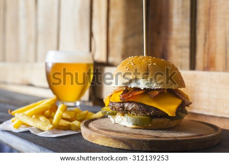 Tasty hamburger with fries and glass of beer on wooden counter. Pickles, bacon, and cheddar cheese - stock photo