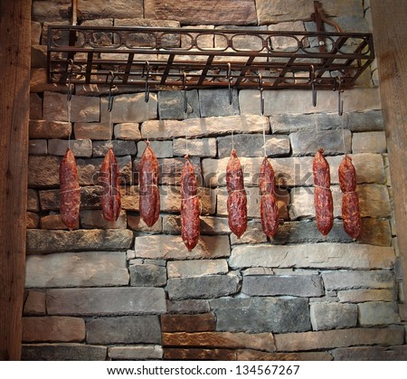 Tasty, hand-made, artisan sausages hanging against a stone wall in a rustic market. - stock photo