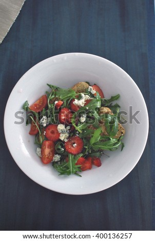 Tasty healthy Mediterranean diet salad Fresh healthy salad in white plate on the blue wooden table.  - stock photo