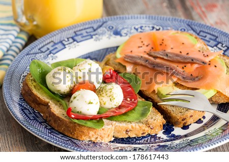 Tasty healthy picnic snacks with whole grain bread topped with gourmet smoked salmon, avocado, mozzarella cheese, chili pepper and baby spinach served on a blue plate - stock photo