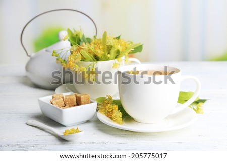 Tasty herbal tea with linden flowers on wooden table - stock photo