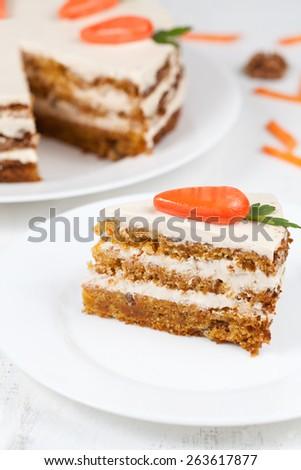 Tasty homemade carrot sponge cake with little orange carrots on topon white background - stock photo