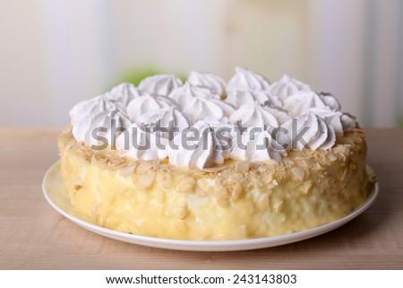 Tasty homemade meringue cake on wooden table, on light background - stock photo