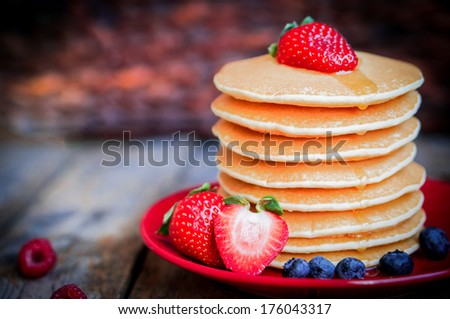 Tasty homemade pancakes with strawberries,blueberries and maple syrup - stock photo