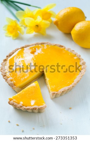 Tasty homemade sweet fruit tart pie with lemon cream filling with narcissus flowers on white table - stock photo