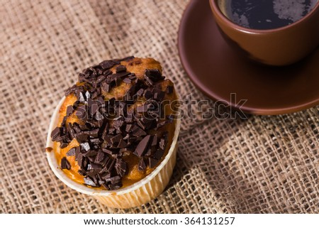 Tasty homemade warm muffin with chocolate pieces and beautiful brown cup of black fragrant coffee on plate lunch time closeup on sackcloth background top view, horizontal picture - stock photo