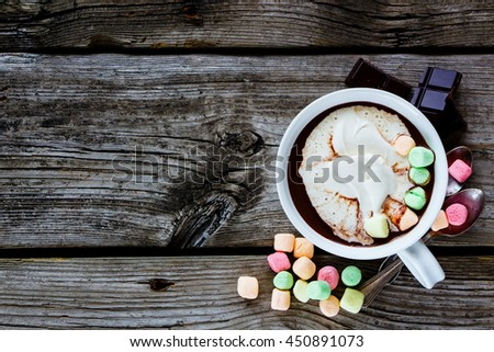 Tasty hot chocolate in white ceramic cup with whipped cream and marshmallows on rustic wooden background. With space for text, top view. - stock photo