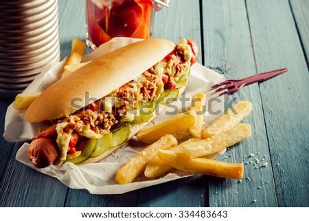 Tasty hot dog with a smoked frankfurter sausage covered with full trimmings on a bed of cucumber on a fresh roll with golden crispy fried potato chips and relish or ketchup on a rustic wooden table - stock photo