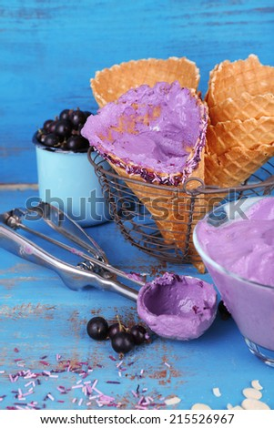Tasty ice cream with fresh berries on old blue wooden table - stock photo