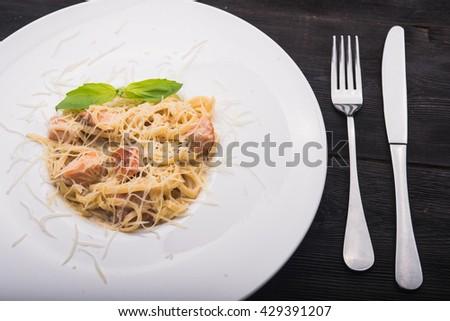 tasty italian pasta with basil leaf on white plate - stock photo