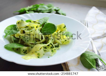 Tasty italian pasta with spinach on white plate - stock photo