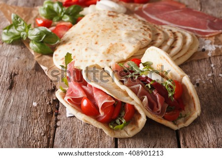 Tasty Italian piadina stuffed with ham, cheese and vegetables close-up on the table. Horizontal - stock photo