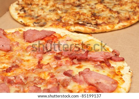 Tasty italian thin crust pizzas with bacon and mozzarella cheese, and mushroom and chicken - stock photo