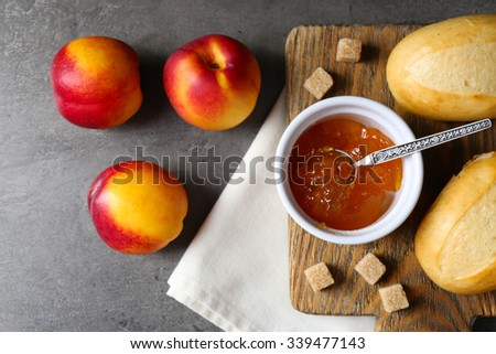 Tasty jam in the bowl, ripe peaches, crackers and fresh buns close-up - stock photo