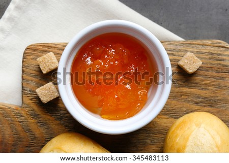 Tasty jam in the jar and bowl, crackers and fresh buns close-up - stock photo