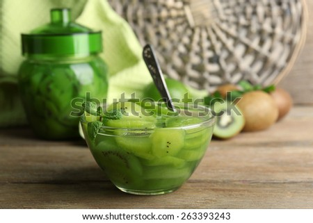 Tasty kiwi jam in glass bowl and jar on wooden table, on wicker mat background - stock photo