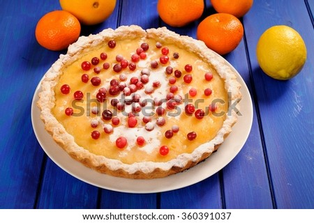 Tasty lemon pie decorated with fresh cranberries and whole orange, lemon and clementines on deep blue table - stock photo
