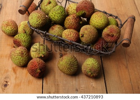 Tasty litchi exotic fruits on wooden background - stock photo